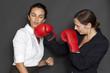 Geschäftfrau schlägt andere Frau mit Boxhandschuh
