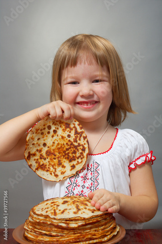 little girl eats pancakes