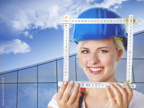 Young female builder takes measurements for housebuilding