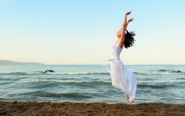The young woman jumps on seacoast