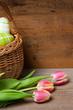 Osterkorb und Tulpen auf Holzbrett