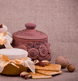 Tasty jam, cupcakes, clay pot and nuts on background