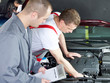 Master mechanic and his worker working on the engine of a car