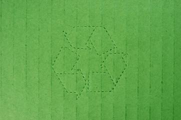 Símbolo de reciclaje sobre cartón verde