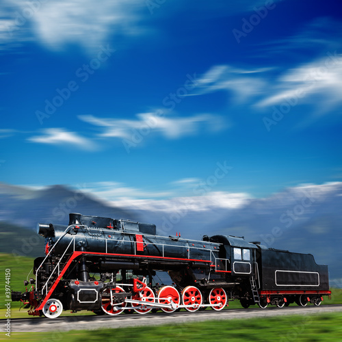 Speeding old locomotive in mountains with motion blur