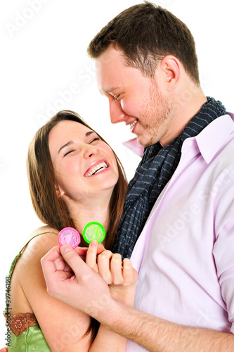 Young couple embracing and holding condoms