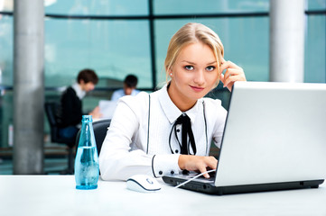 Portrait of beautiful woman using laptop at her workplace
