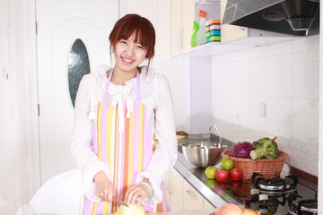 A Chinese woman is cooking  various kinds vegetable.