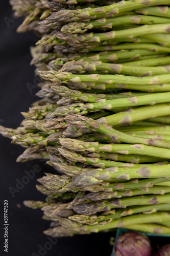 Freshly harvested organic asparagus spears with purple artichoke