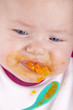 baby girl eating her first mashed carrot