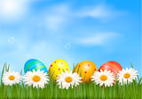 Easter eggs laying in grass with daisy under sky