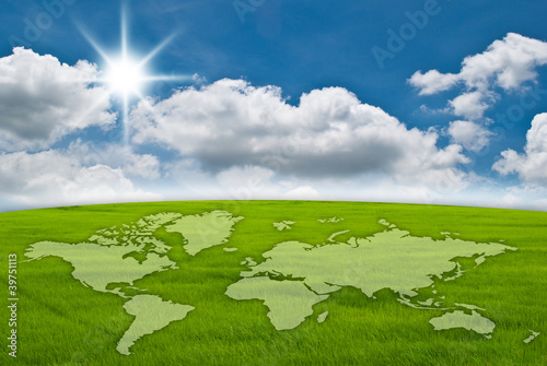 World map on grass field and blue sky.