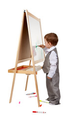 A child paints on an easel in the studio