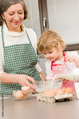 Grandmother and granddaughter prepare dough