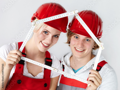 Pretty young couple in overalls with yardstick