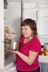 woman eating  from pan near  fridge