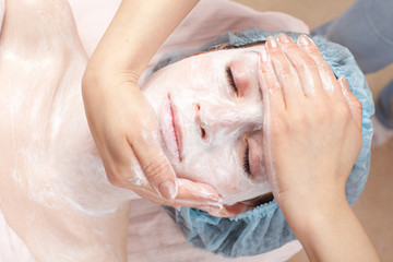 Beautiful woman with facial mask getting beauty treatment at sal
