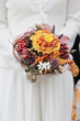Bride holding beautiful orange wedding flowers bouquet