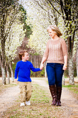 Mother and son walking hand in hand at park