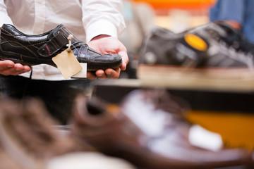 Man buying sneakers in supermarket