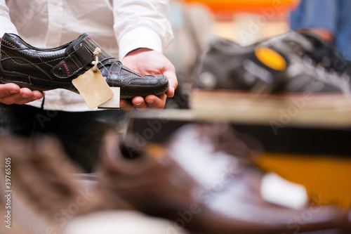 Man buying sneakers in supermarket