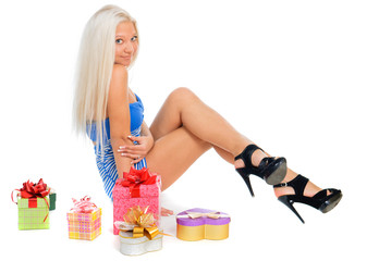 Beautiful sexy blond woman in blue dress with present boxes on w