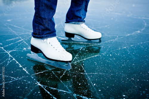 Young woman ice skating outdoors on a pond on a freezing winter