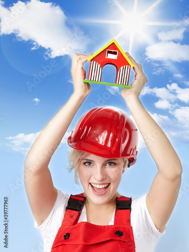 Happy young female worker in overall presents a toy house