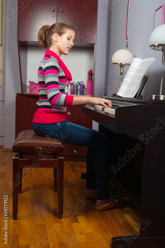 Pretty teenage girl playing on piano in her room