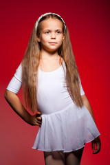 Little ballet dancer isolated on a red background