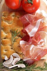 pizza focaccia con prosciutto pomodori e funghi