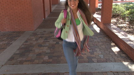 Happy latina student walking towards camera