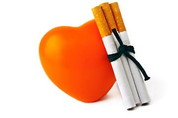 Orange heart, three cigarettes, isolated on white background.