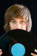 Portrait of a young man hiding behind a vinyl record