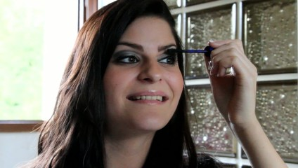 femme appliquant du mascara