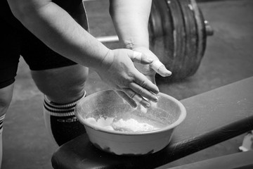 Closeup of hands of the powerlifter in talc