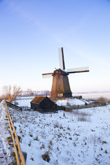 Windmill in winter time with snow and blue sky