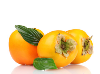 Three appetizing persimmons with green leaves isolated on white