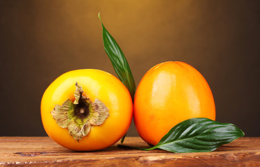 Two appetizing persimmons on wooden table on brown background