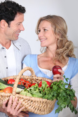 Couple looking into each other's eyes with vegetable basket.