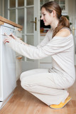 Housework: young woman using a dishwasher