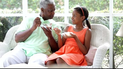 Black grandfather and granddaughter having ice cream on the porch