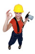 Tradeswoman holding a blowtorch and giving the a-ok sign