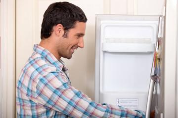 Man opening fridge door