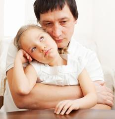 Father comforts a sad girl
