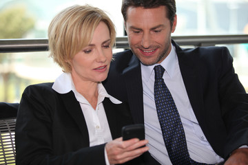 Businessman and woman looking at phone