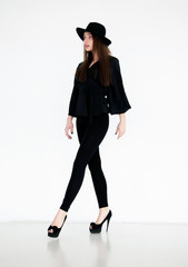 Elegant beautiful woman in black clothing and hat isolated