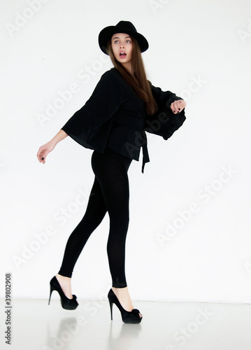 Beautiful young model girl in black hat on the white background