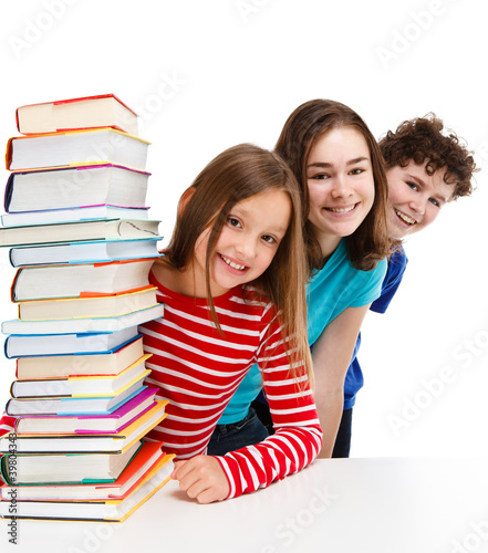 Students peeking behind pile of books on white