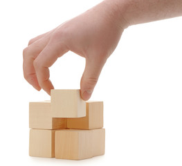 The hand establishes a wooden cube